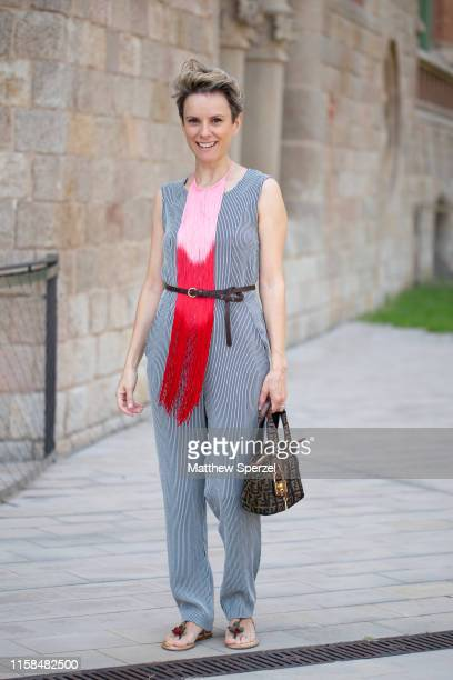 A guest is seen on the street attending 080 Barcelona Fashion Week wearing grey outfit with pink/red scarf and black belt with Fendi bag on June 26...