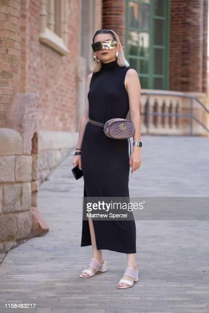 A guest is seen on the street attending 080 Barcelona Fashion Week wearing black sleeveless dress hip belt bag white heels on June 26 2019 in...