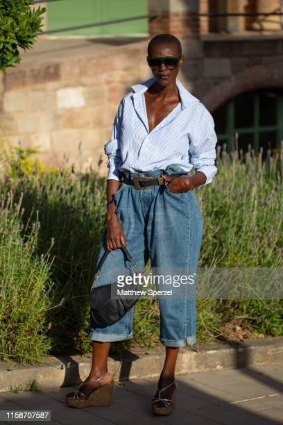 A guest is seen on the street attending 080 Barcelona Fashion Week wearing blue shirt highwaisted blue jeans black belt and black Dior bag on June 27...