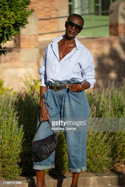 Guest is seen on the street attending 080 Barcelona Fashion Week wearing blue shirt, high-waisted blue jeans, black belt and black Dior bag on June...