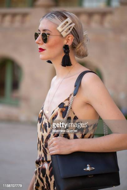 A guest is seen on the street attending 080 Barcelona Fashion Week wearing leopard print dress black Vivienne Westwood bag pearl barrettes black...