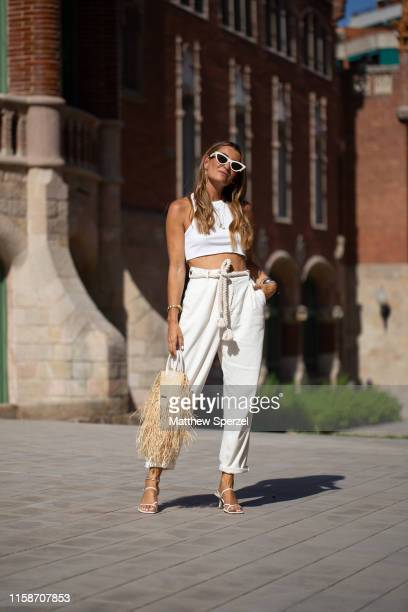 A guest is seen on the street attending 080 Barcelona Fashion Week wearing white crop top white highwaist pants and a Jacquemus straw bag on June 27...