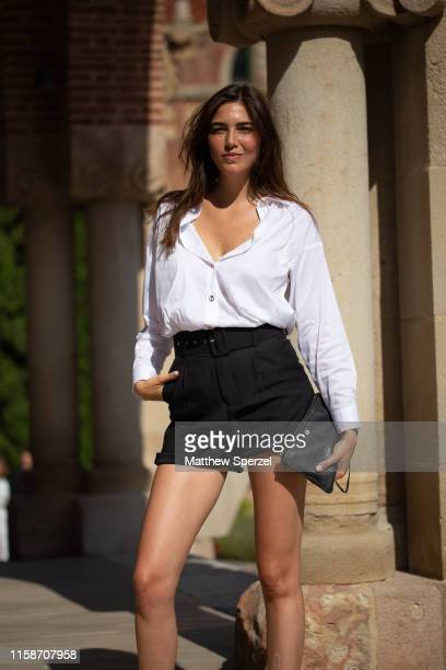 A guest is seen on the street attending 080 Barcelona Fashion Week wearing white buttondown shirt with black shorts and strappy black sandals on June...