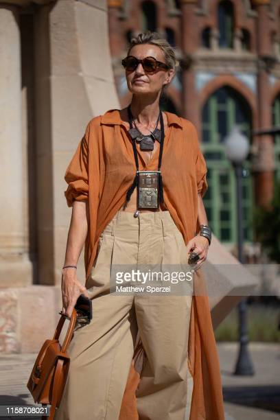 A guest is seen on the street attending 080 Barcelona Fashion Week wearing copper long shirt various necklaces khaki highwaisted pants and brown...