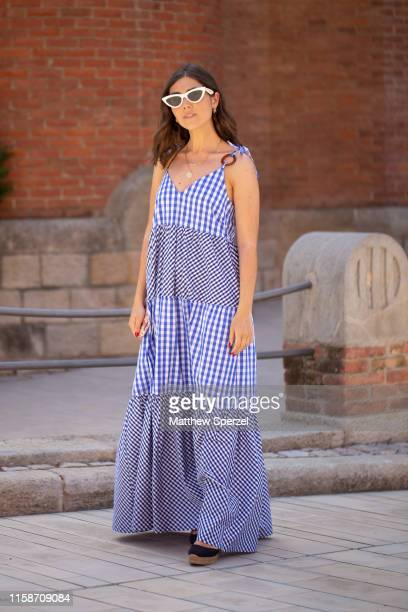 Guest is seen on the street attending 080 Barcelona Fashion Week wearing blue checker maxi dress and white retro sunglasses on June 27, 2019 in...