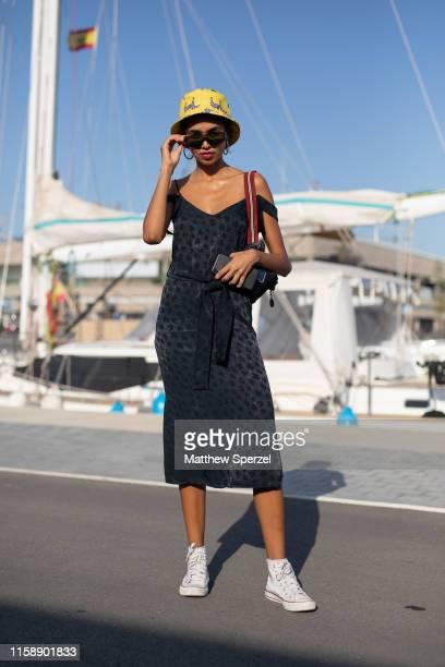 Guest is seen on the street attending 080 Barcelona Fashion Week wearing black dress with yellow bucket hat on June 28, 2019 in Barcelona, Spain.