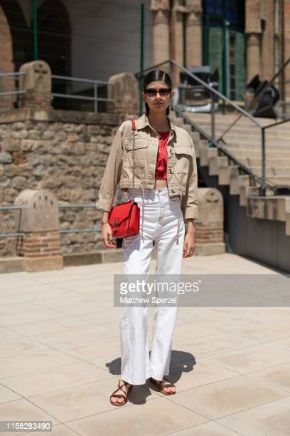 A guest is seen on the street attending 080 Barcelona Fashion week wearing tan jacket red crop top red bag and white pants with sandals on June 25...