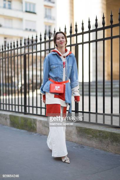 A guest is seen on the street attending AALTO during Paris Fashion Week Women's A/W 2018 Collection wearing a denim jacket with cream hoodie and red...
