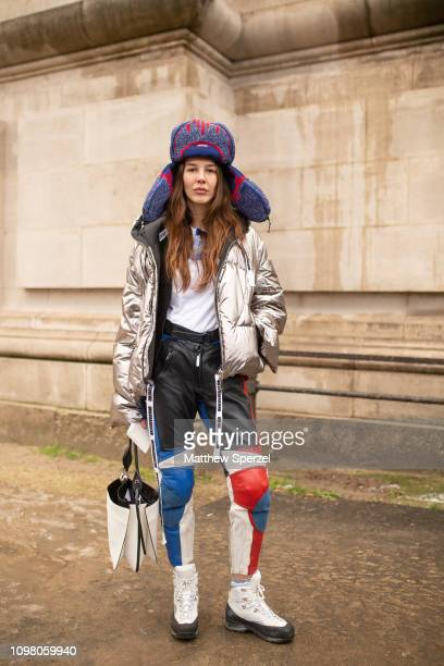 A guest is seen on the street attending ALEXANDRE VAUTHIER during Paris Haute Couture Fashion Week wearing navy/red large hat silver metallic coat...