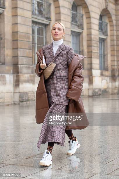 A guest is seen on the street attending Alexis Mabille during Paris Haute Couture Fashion Week wearing grey suit with brown leather coat and...