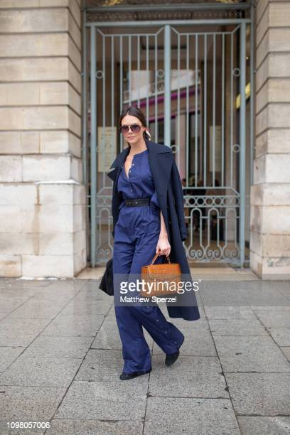 Guest is seen on the street attending Alexis Mabille during Paris Haute Couture Fashion Week wearing navy wool coat and navy jumpsuit with tan bag...
