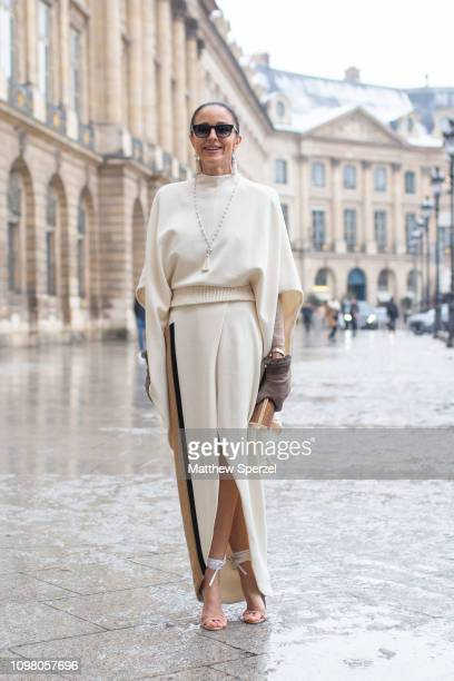 A guest is seen on the street attending Alexis Mabille during Paris Haute Couture Fashion Week wearing cream dress brown gloves and white heels with...