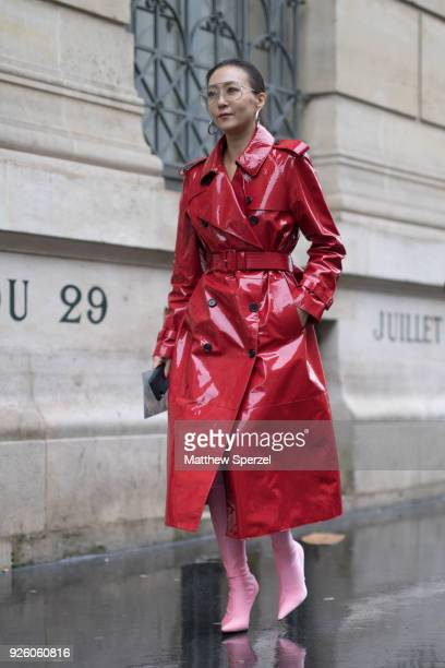 A guest is seen on the street attending Ann Demeulemeester during Paris Fashion Week Women's A/W 2018 Collection wearing a long red vinyl coat with...