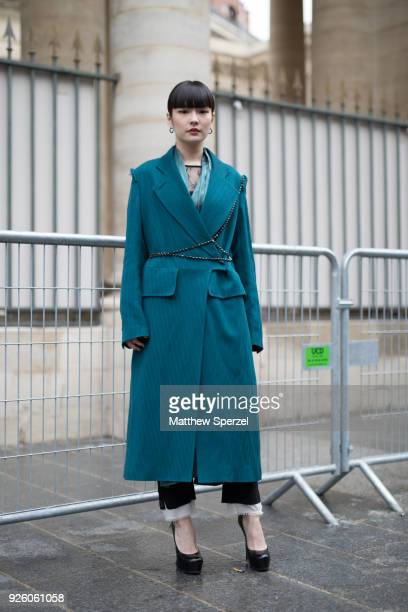 A guest is seen on the street attending Ann Demeulemeester during Paris Fashion Week Women's A/W 2018 Collection wearing a long teal coat with black...