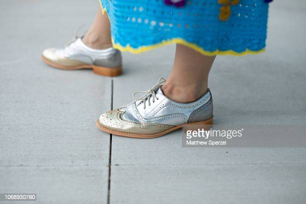 A guest is seen on the street attending Art Basel Private Day during Miami Art Week wearing blue knit outfit silver shoes and gold knit bag on...