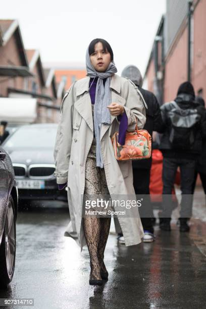 A guest is seen on the street attending Balenciaga during Paris Women's Fashion Week A/W 2018 wearing a grey head scarf with snakeskin skirt on March...