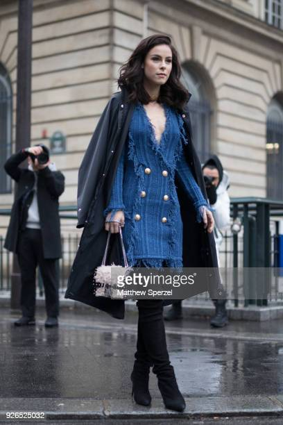 A guest is seen on the street attending Balmain during Paris Fashion Week Women's A/W 2018 Collection wearing a blue fringe dress with black...