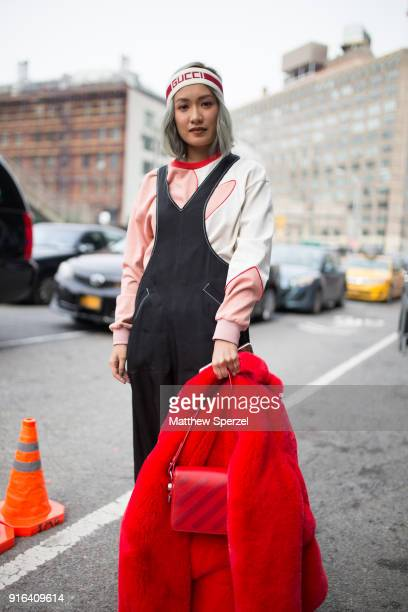 A guest is seen on the street attending Bibhu Mohapatra during New York Fashion Week wearing a Gucci headband red coat and bag with black overalls on...