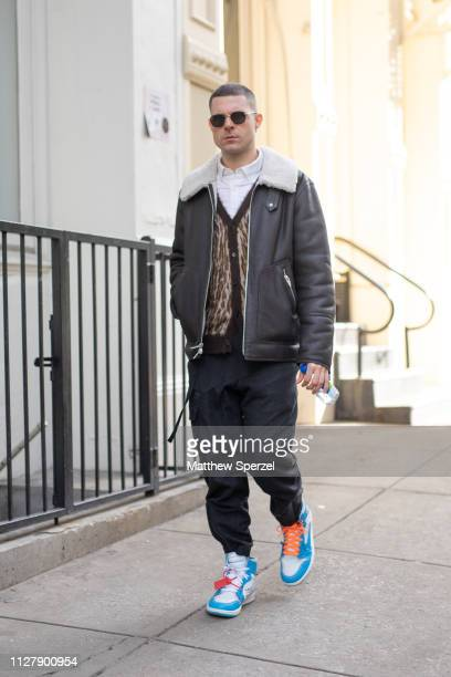 A guest is seen on the street attending Bode during Men's Fashion Week New York wearing black leather jacket brown vest white shirt black pants and...