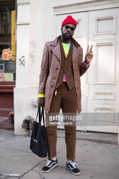 A guest is seen on the street attending Bode during Men's Fashion Week New York wearing red beanie brown coat brown vest and pants tiedye shirt black...