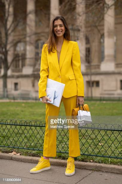 A guest is seen on the street attending CHANEL during Paris Fashion Week AW19 wearing CHANEL yellow blazer and pants with yellow sneakers on March 05...