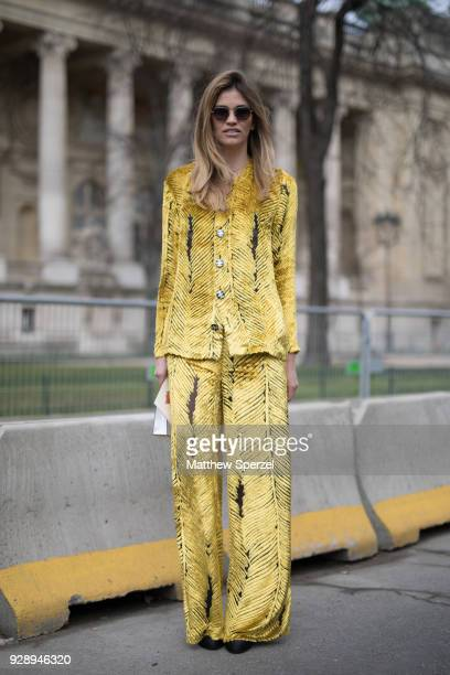 A guest is seen on the street attending Chanel during Paris Women's Fashion Week A/W 2018 wearing a yellow suit on March 6 2018 in Paris France