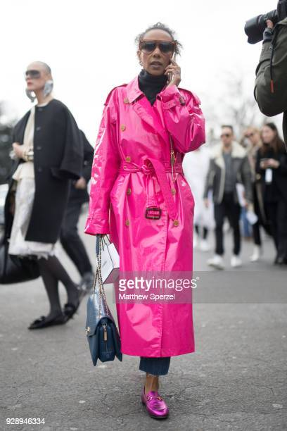 A guest is seen on the street attending Chanel during Paris Women's Fashion Week A/W 2018 wearing a pink nylon trenchcoat with pink loafers on March...
