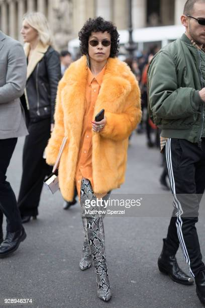 A guest is seen on the street attending Chanel during Paris Women's Fashion Week A/W 2018 wearing yellow fur coat with yellow shirt and thighhigh...