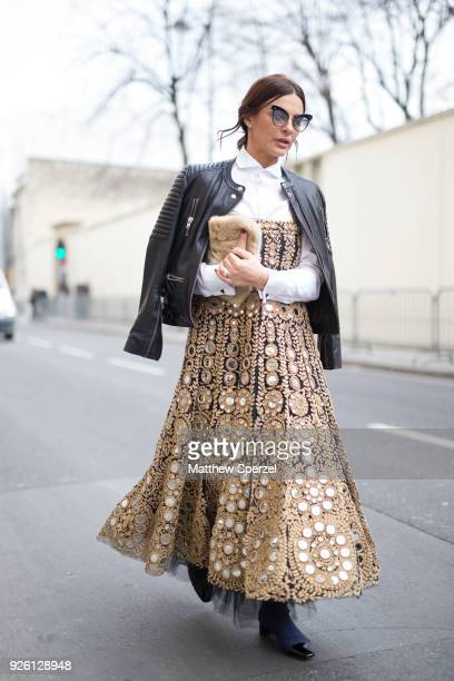 A guest is seen on the street attending Christian Dior during Paris Fashion Week Women's A/W 2018 Collection wearing a gold Dior dress with black...
