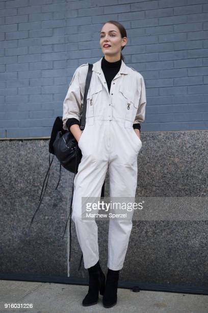 A guest is seen on the street attending Colovos and Noon By Noor during New York Fashion Week wearing an offwhite jumpsuit and black bag on February...