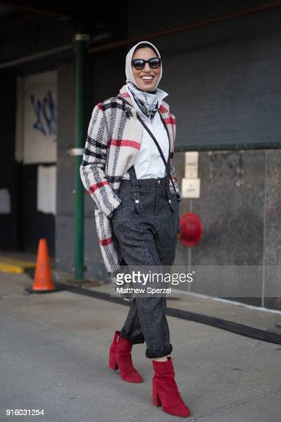 Guest is seen on the street attending Colovos and Noon By Noor during New York Fashion Week wearing a plaid coat with grey trousers and suspenders...