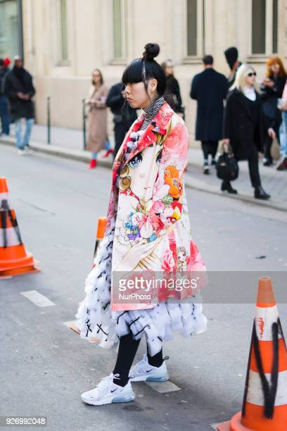 A guest is seen on the street attending Comme des Garons during Paris Women's Fashion Week A/W 2018 wearing a multicolor floral print outfit on...