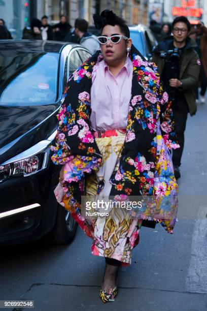 A guest is seen on the street attending Comme des Garons during Paris Women's Fashion Week A/W 2018 wearing a multicolor floral print outfit with...