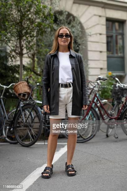 Guest is seen on the street attending Copenhagen Fashion Week SS20 wearing black leather jacket, bone shorts, white tshirt, black sandals on August...