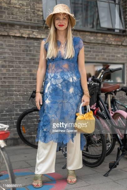 Guest is seen on the street attending Copenhagen Fashion Week SS20 wearing blue sheer dress, silver pants, yellow bag, straw bucket hat on August 07,...