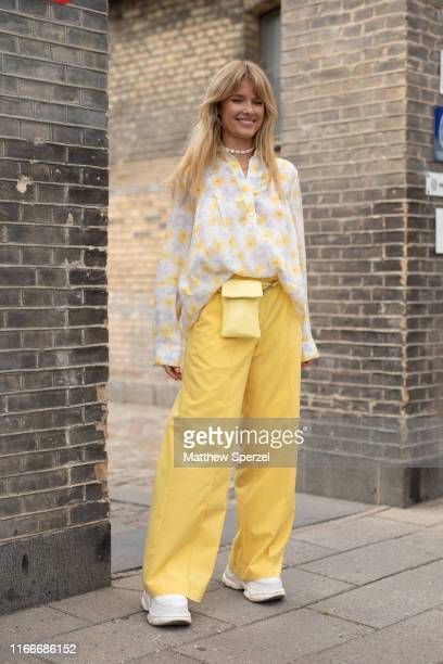 A guest is seen on the street attending Copenhagen Fashion Week SS20 wearing floral print top with yellow pants lemon yellow hip belt bag white...