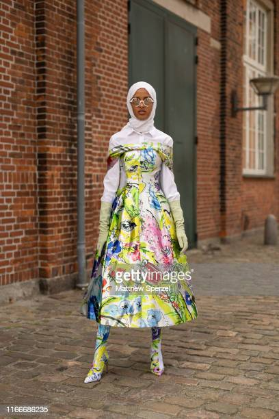 Guest is seen on the street attending Copenhagen Fashion Week SS20 wearing white hijab, colorful design dress and shoes on August 07, 2019 in...