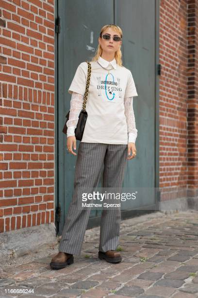 A guest is seen on the street attending Copenhagen Fashion Week SS20 wearing white graphic shirt button down collared shirt grey slacks black bag and...