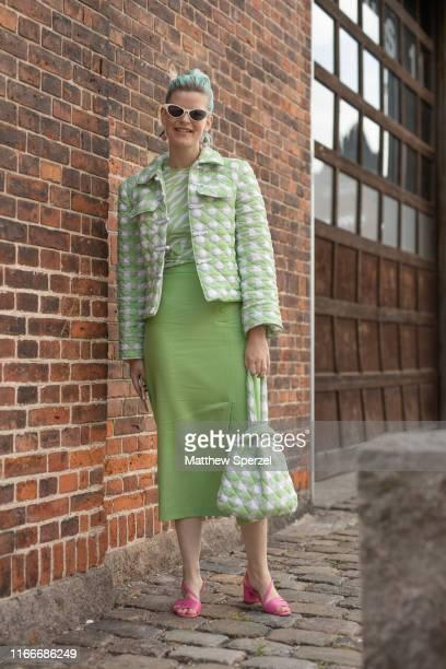 Guest is seen on the street attending Copenhagen Fashion Week SS20 wearing white/green pattern jacket and bag, green/white striped shirt, green skirt...