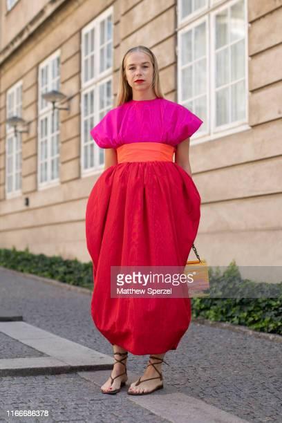 Guest is seen on the street attending Copenhagen Fashion Week SS20 wearing pink/red dress with orange belt and bag on August 07, 2019 in Copenhagen,...
