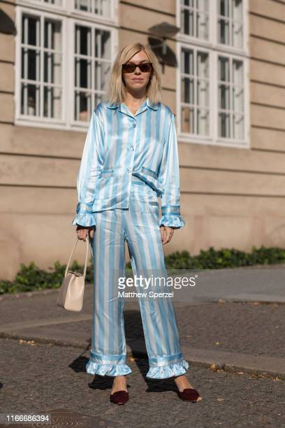 Guest is seen on the street attending Copenhagen Fashion Week SS20 wearing silk blue/white stripe outfit with taupe bag and sunglasses on August 07,...