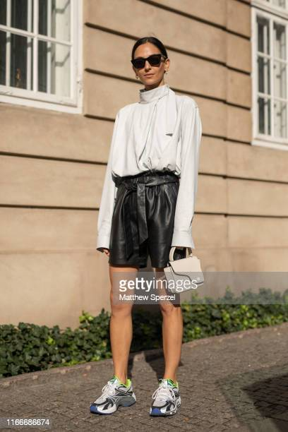 Guest is seen on the street attending Copenhagen Fashion Week SS20 wearing white long sleeve top, black leather shorts, taupe bag, sneakers on August...