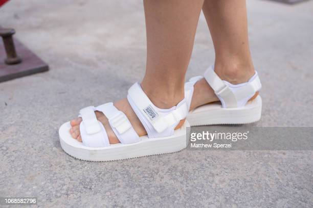 A guest is seen on the street attending Design Miami Preview Day during Miami Art Week wearing white outfit gold snake bracelet strawberry bag and...