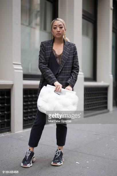A guest is seen on the street attending EDUN during New York Fashion Week wearing a tweed jacket with white pillow purse on February 14 2018 in New...