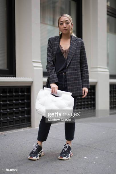 Guest is seen on the street attending EDUN during New York Fashion Week wearing a tweed jacket with white pillow purse on February 14, 2018 in New...