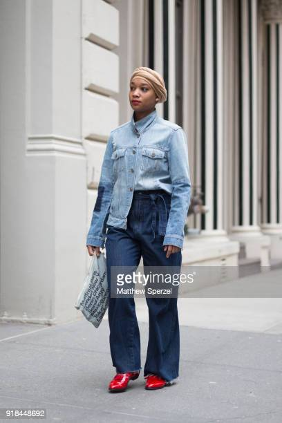 A guest is seen on the street attending EDUN during New York Fashion Week wearing a light blue navy jacket with dark blue denim pants and red shoes...