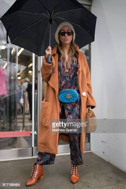 A guest is seen on the street attending Gemma Hoi during New York Fashion Week wearing a tan long coat black/green/burgundy outfit brown leather...