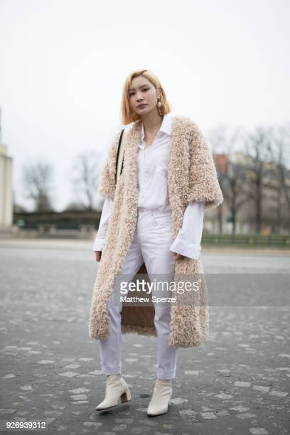 A guest is seen on the street attending Haider Ackermann during Paris Women's Fashion Week A/W 2018 wearing a beige shag coat with white outfit on...