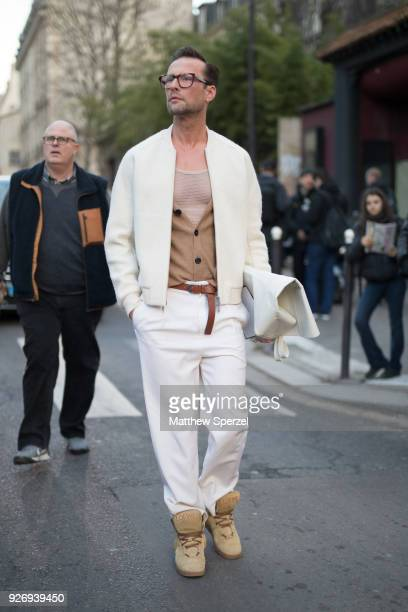 A guest is seen on the street attending Herms during Paris Women's Fashion Week A/W 2018 wearing a cream sweater white pants camel vest mesh shirt...