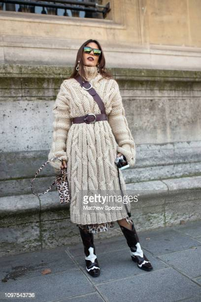 A guest is seen on the street attending Iris van Herpen during Paris Haute Couture Fashion Week wearing cream knit coat brown leather belts cowgirl...
